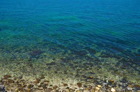 A coast with stones and blue ocean water. photo