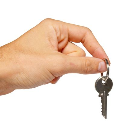 Silver key in a hand isolated on white. Stock Photo - 3667422