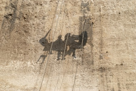 Human shadows on the bright yellow rock photo