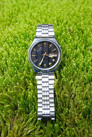 Mans watch on the grass field. photo