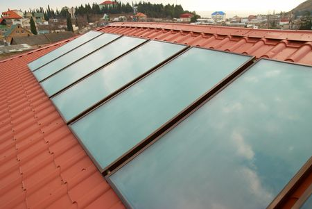 Solar water heating system (geliosystem) on the red house roof. photo