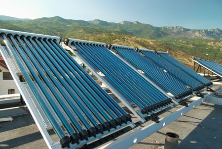 Vacuum solar water heating system on the house roof. Stock Photo - 5185211