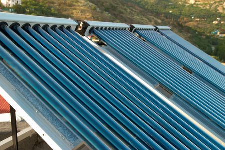 Vacuum solar water heating system on the house roof. photo