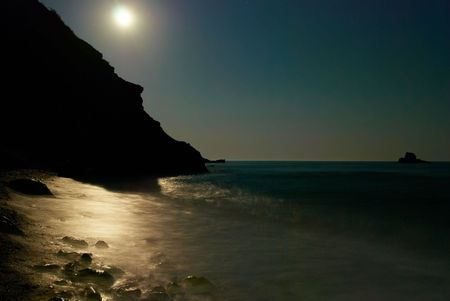 Moon night on the sea with waves and rocks. photo