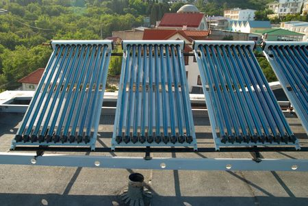 Vacuum solar water heating system on the house roof. Stock Photo - 5217872