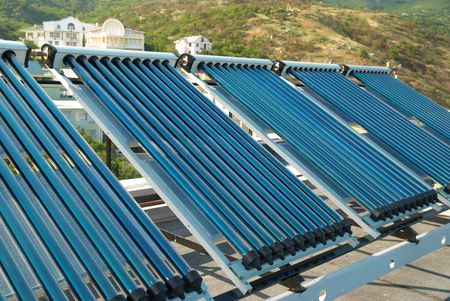 Vacuum solar water heating system on the house roof. Stock Photo - 5234205