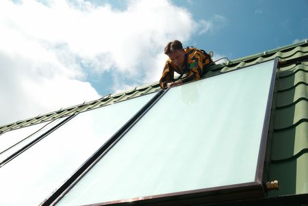 house worker: Erector of solar water heating system on the roof. Stock Photo