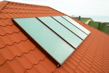 Solar water heating system (geliosystem) on the red house roof. Stock Photo - 5650100
