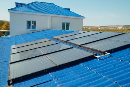 toiture maison: Chauffe-eau solaire sur le toit de la maison de chauffage.