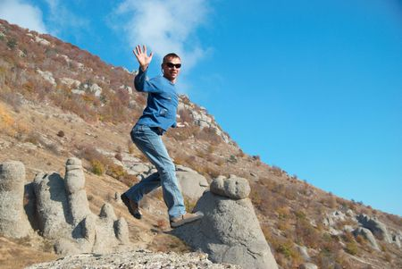 Man jumping on the rocks with landscape background Stock Photo - 6000952