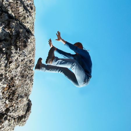 Falling down man from the rock with blue background photo