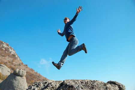 Man jumping on the rocks with landscape background Stock Photo - 6000946