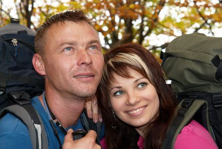 Young tourist couple in the autumn park with rucksacks Stock Photo - 6068783