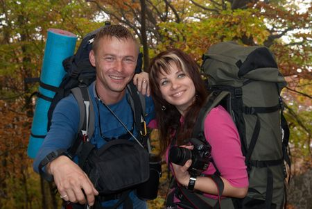 Young tourist couple in the autumn park with rucksacks Stock Photo - 6068800