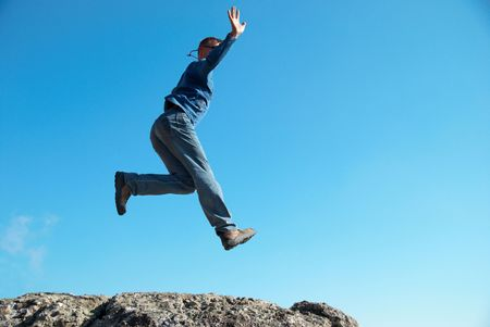 Man jumping on the rocks with landscape background Stock Photo - 6068785