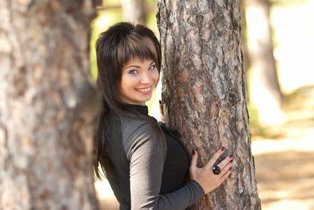 Pretty woman near tree in the park photo