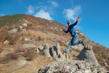 Man jumping on the rocks with landscape background Stock Photo - 6174795