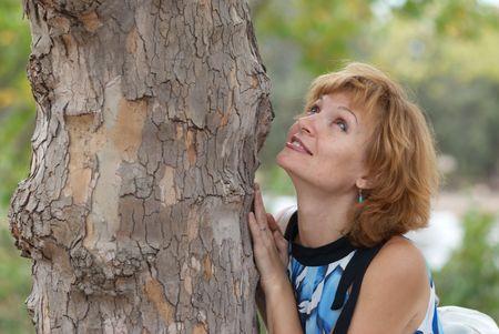 Beautiful woman near tree, with soft background photo