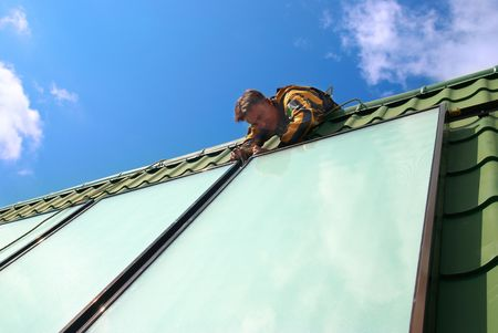 Erector of solar water heating system on the roof. Stock Photo