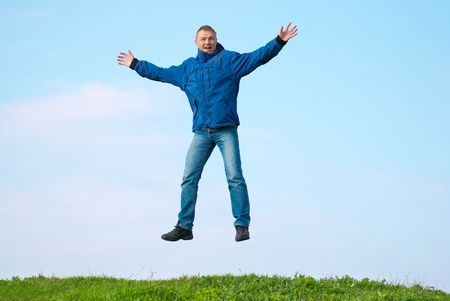 Jumping man on the hill with green grass Stock Photo - 6875846
