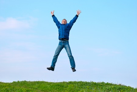 Jumping man on the hill with green grass Stock Photo - 7033958