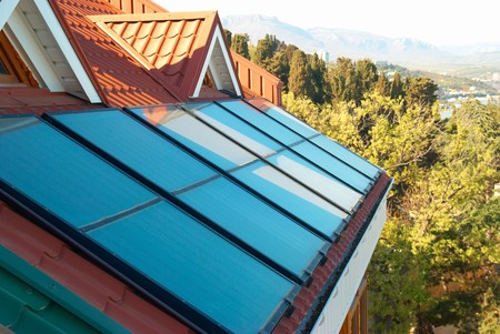 toiture maison: Syst�me solaire sur le toit de la maison rouge Banque d'images