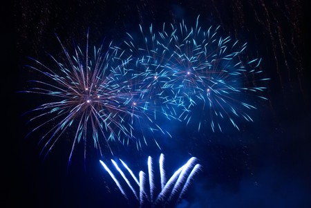 Blue fireworks on the black sky background photo
