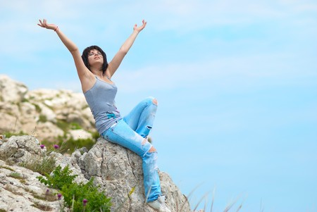 Pretty young woman relaxing on the rock Stock Photo - 7338284