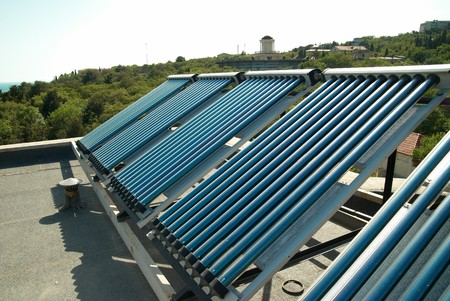 Vacuum solar water heating system on the house roof. Stock Photo - 7395792