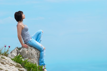 Pretty young woman relaxing on the rock Stock Photo - 7502750