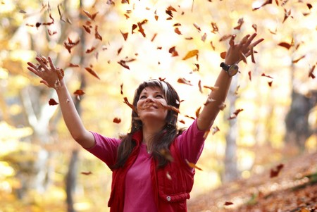 Beautiful girl with falling leaves in the autumn park photo