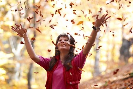 hojas secas: Hermosa chica con hojas ca�das en el Parque de oto�o