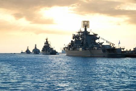 azul marino: Fila de barcos militares contra atardecer marino  Foto de archivo