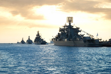 warship: Row of military ships against marine sunset Stock Photo