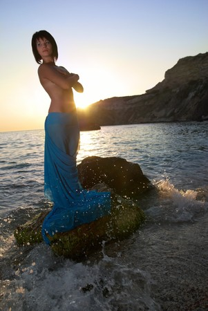 Pretty woman on the sea rock against sunset. photo