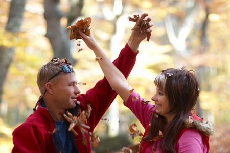 Young couple enjoying the falling leaves in the autumn park Stock Photo - 7878287