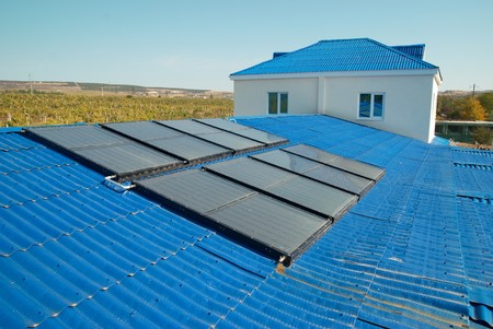 Solar water heating system on the house roof. photo