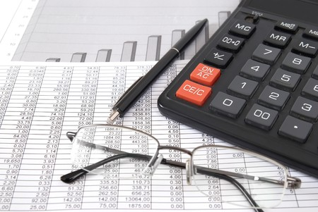 financial paperwork: Pen, glasses and calculator on paper table with finance diagram Stock Photo