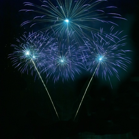 Blue fireworks on the black sky background photo