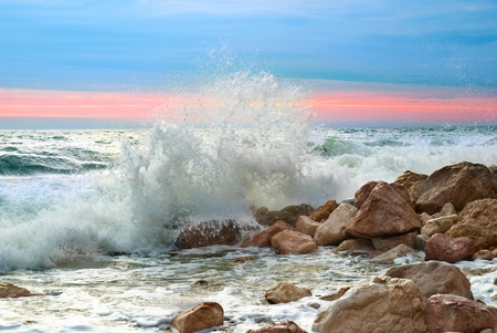 Sea landscape with waves on the beach against sunset photo