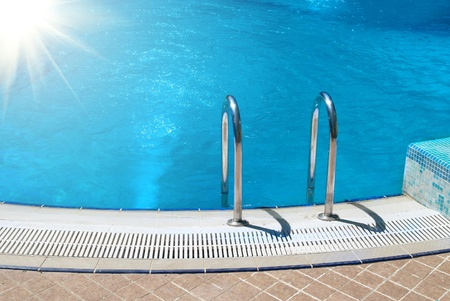 hotel resort: Swimming pool with stair and blue relaxing water Stock Photo