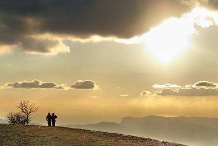 femme romantique: Couple sur la colline contre le coucher du soleil. Paysage avec le ciel et les nuages.
