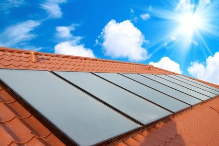 Sistema di riscaldamento solare dell'acqua sul tetto rosso. Gelio pannelli.