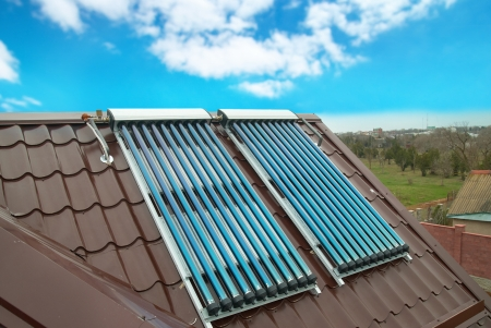 Vacuum solar water heating system on the house roof. Stock Photo - 9586855