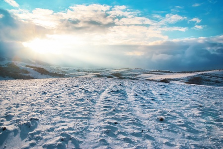 Winter hills covered by snow against sunset photo