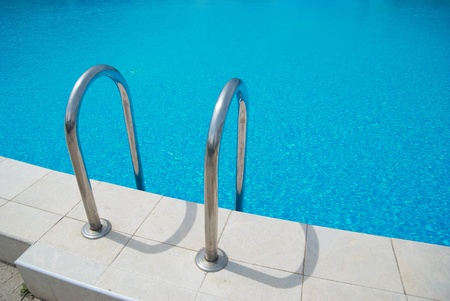 Swimming pool with stair and blue relaxing water photo