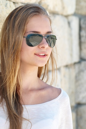 blonde teenager: Beautiful blond girl in the goggles against the ancient wall Stock Photo
