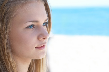 Beautiful blond hair girl with blue eyes outdoors against the sea photo