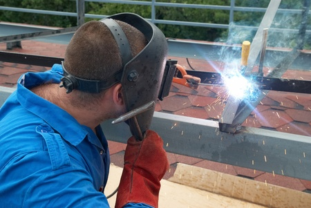 Welder at the factory working with metal construction photo