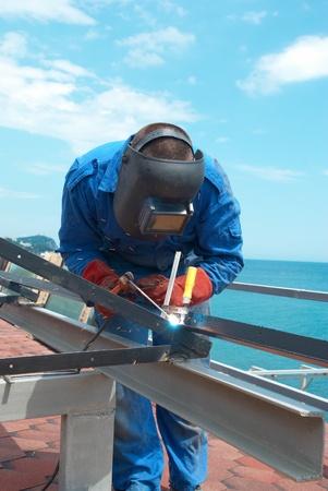 soldadura: Soldador en la fábrica trabajando con la construcción del metal